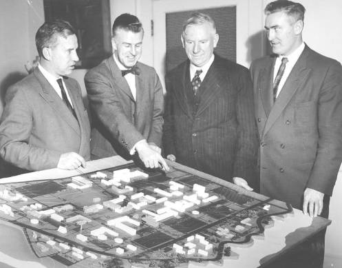 Roy Jessiman points out interesting features of relief map showing future development at UBC, 1958. Left to right: Geoffrey Andrew, Roy Jessiman, Norman Mackenzie, T.S. Hughes. UBC Archives.